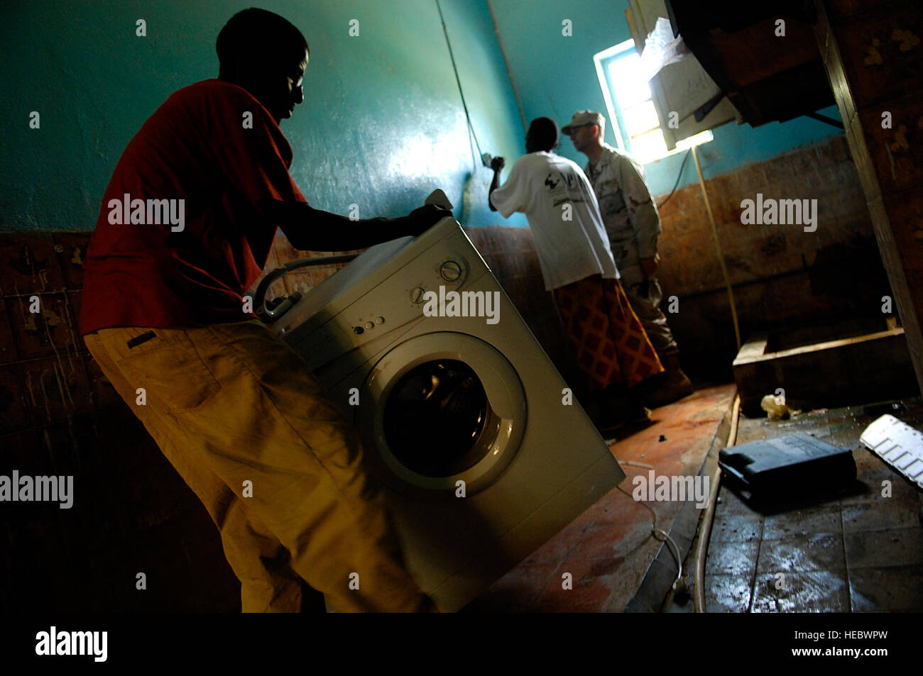With the help of a Djiboutian orphan, Builder 1st Class Mark Gerth prepares to install a washing machine during - Stock Image