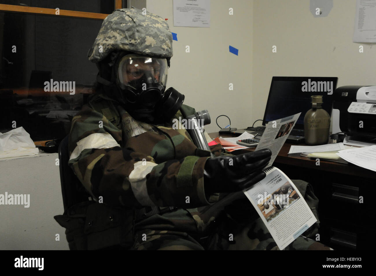 A U.S. Airman clad in a chemical protective overgarment checks over paperwork while waiting out a post attack assessment - Stock Image
