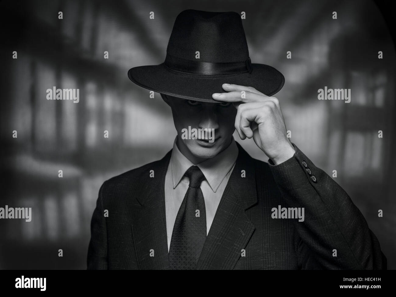 The detective takes on the camera. Vintage style black and white image of a polite young man in a suit doffing his - Stock Image