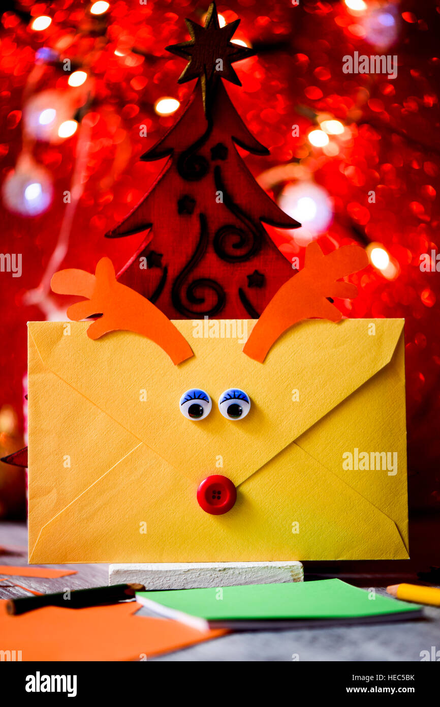 closeup of an envelope customized as a reindeer face with a button as nose and paperboard antlers, containing a - Stock Image