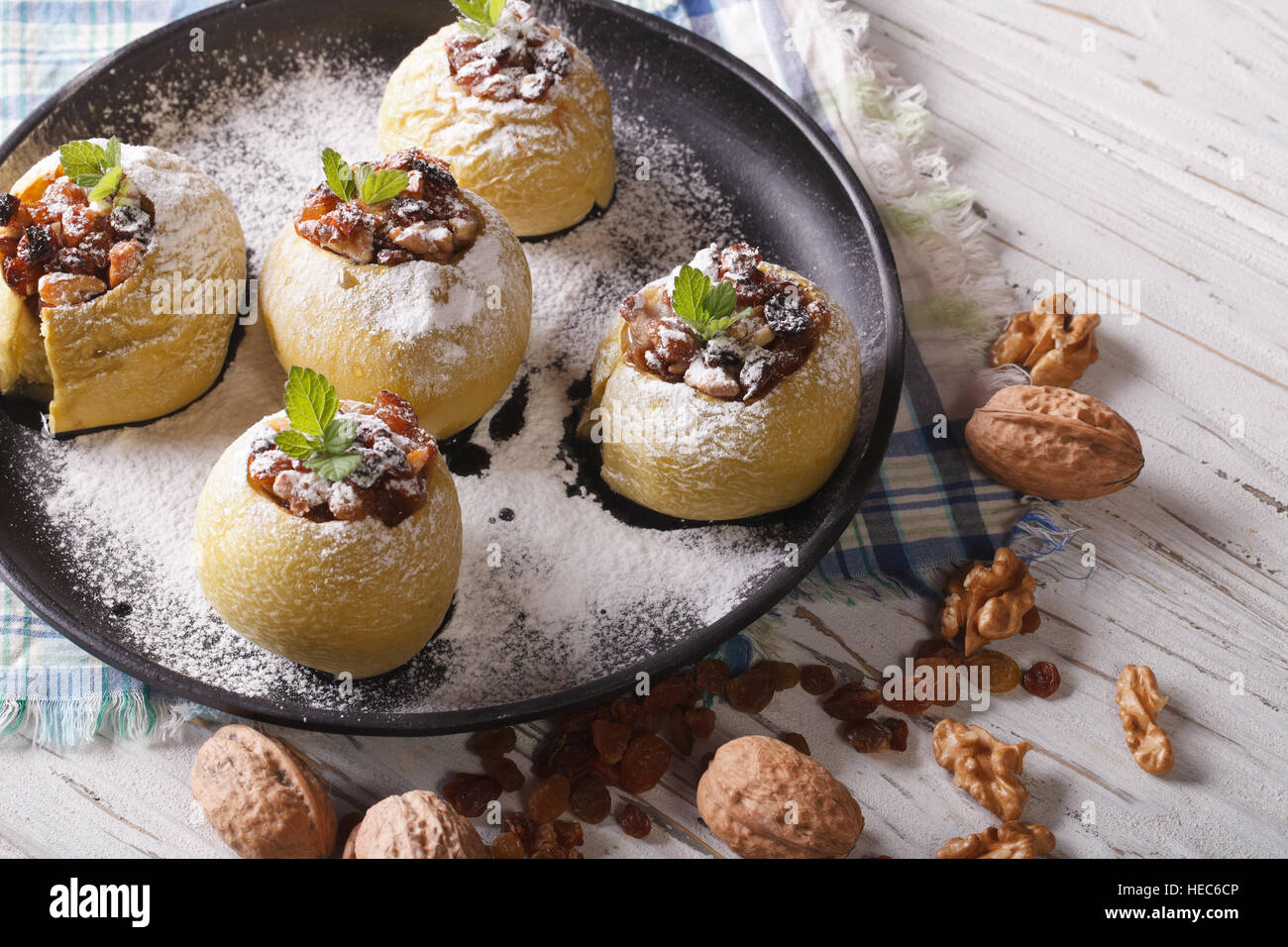 Delicious baked apples with raisins, walnuts and honey on a plate close-up horizontal - Stock Image