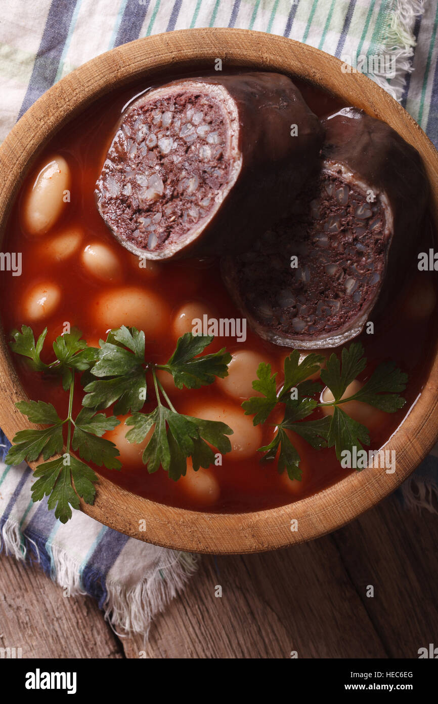Bean soup with sausage Morcillo close up in a bowl. vertical top view Stock Photo