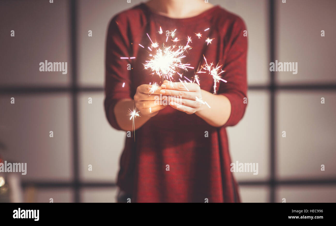 Woman Holding Sparklers in Christmas setting Stock Photo
