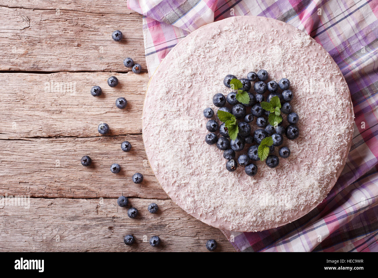 blueberry cheesecake with mint and coconut on the table. horizontal view from above - Stock Image