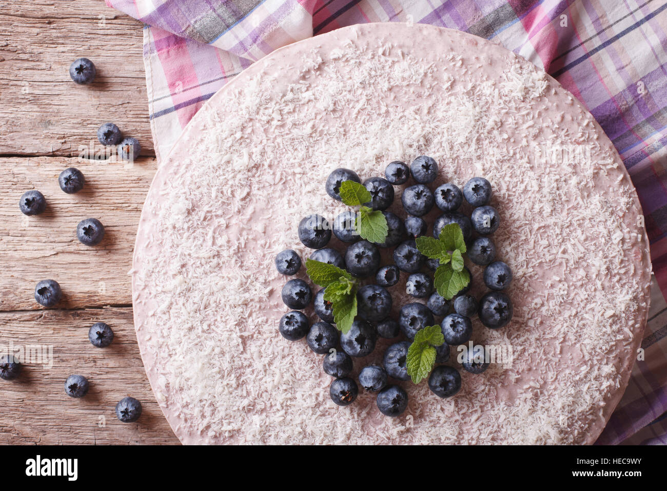 blueberry cheesecake with mint and coconut on the table close-up. horizontal view from above - Stock Image