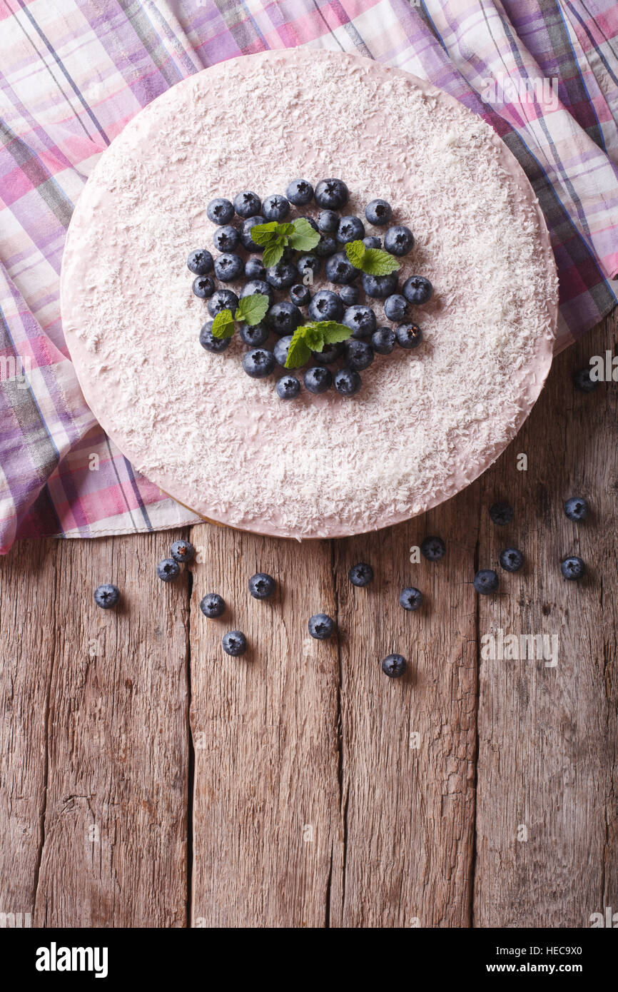 blueberry cheesecake with mint and coconut on the table. vertical top view - Stock Image