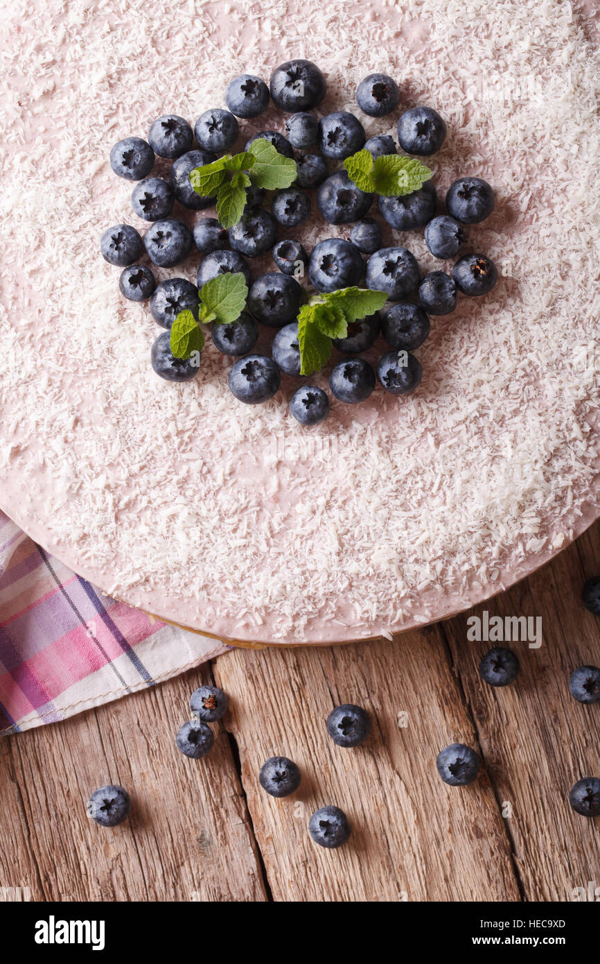 Delicious blueberry cheesecake with coconut and mint close-up on the table. vertical top view - Stock Image