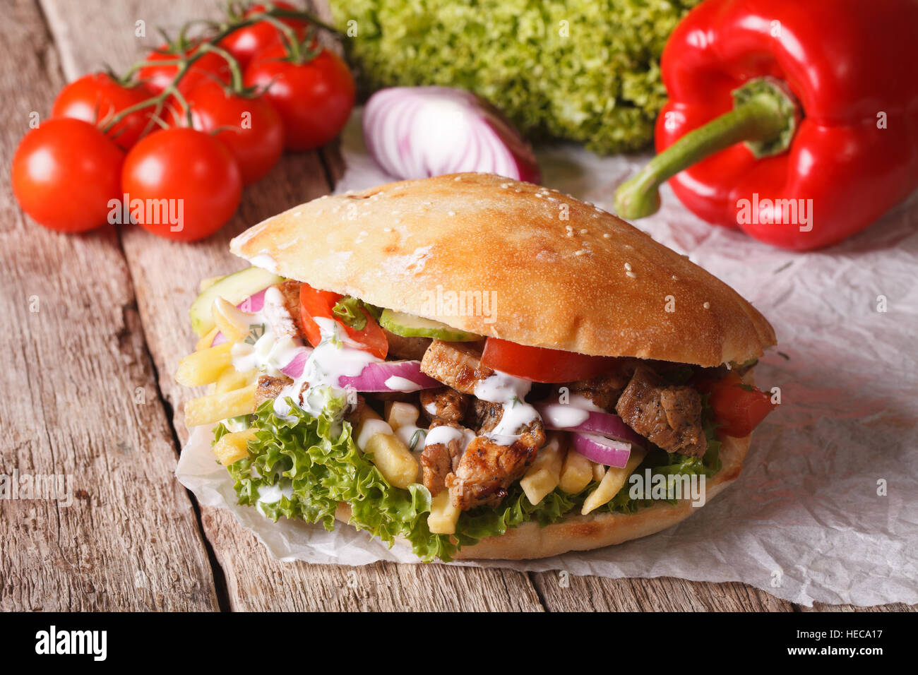 Fast Food: Doner kebab with meat, vegetables and french fries close-up on the table. horizontal - Stock Image