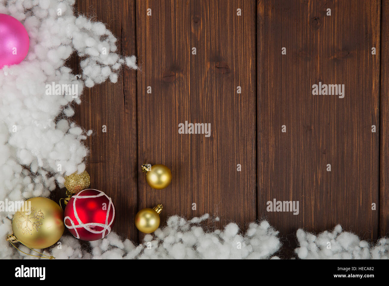 Colored christmas balls and snow decoration on old wooden background - Stock Image