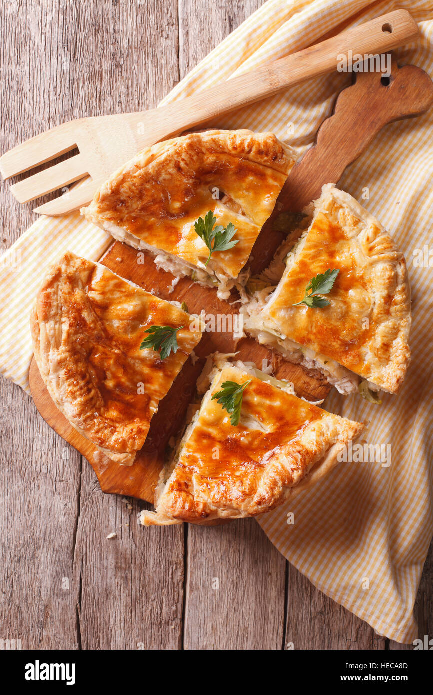 Rustic sliced chicken pie close-up on the table. vertical view from above - Stock Image