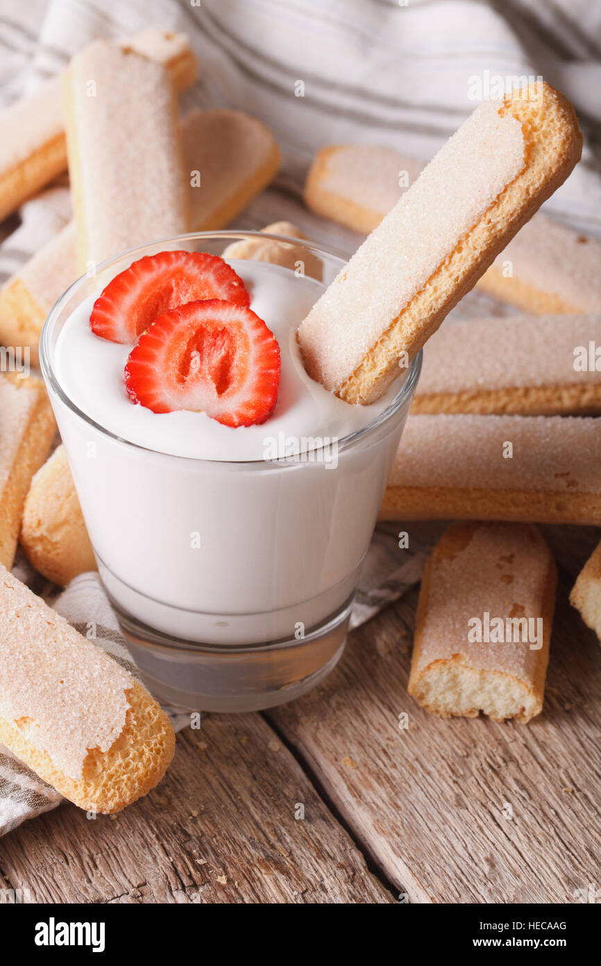 Savoiardi delicious cookies with strawberries yogurt in a glass. vertical - Stock Image