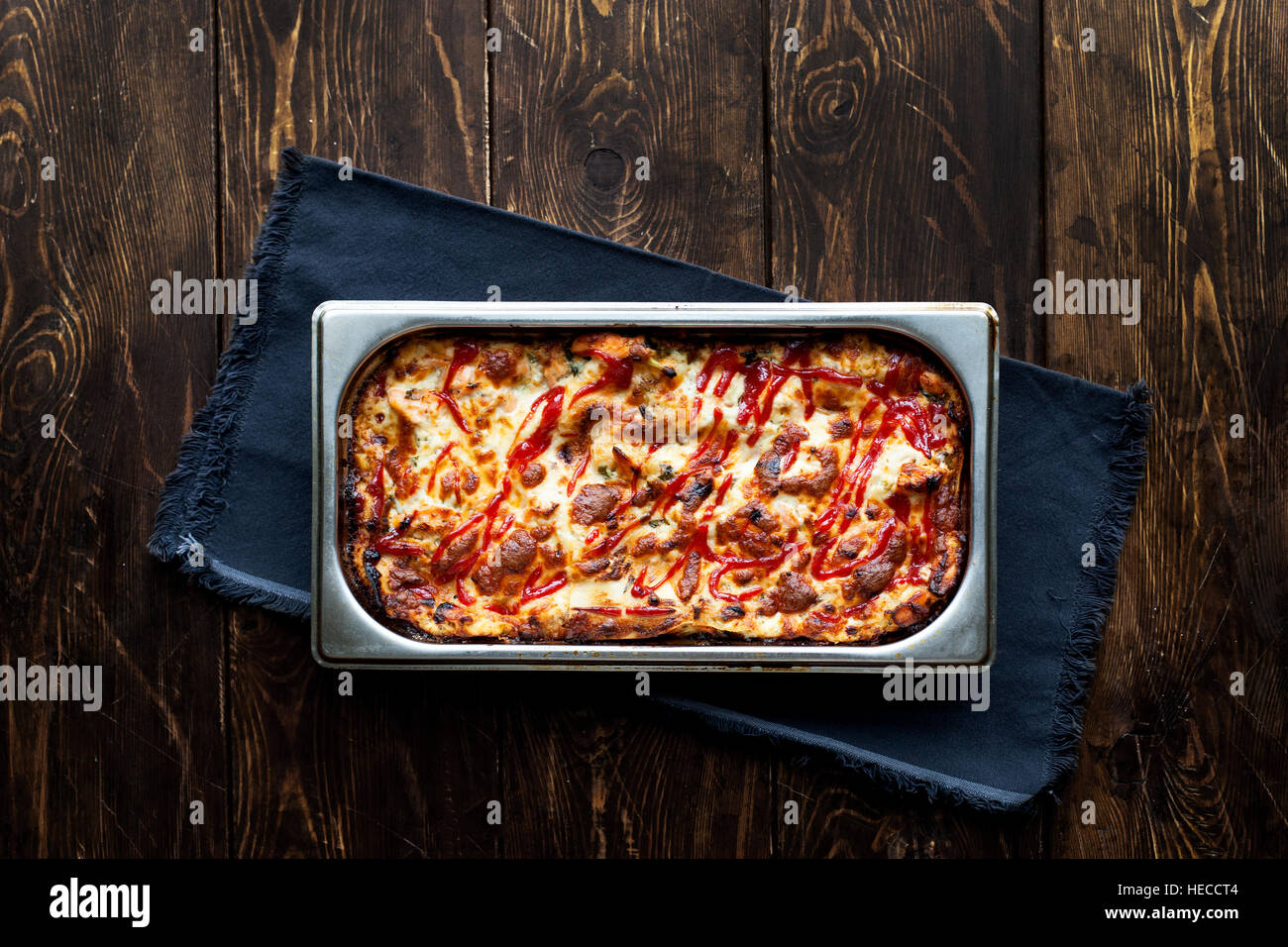Italian Food. Hot tasty lasagna in ceramic casserole dish on Wooden Table - Stock Image