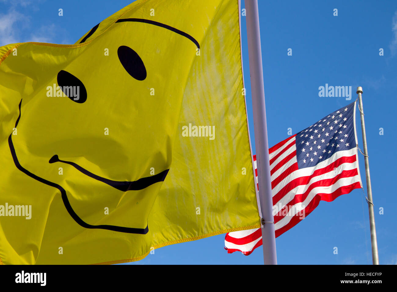 Smiley faced flag and flag of the United States of America - Stock Image