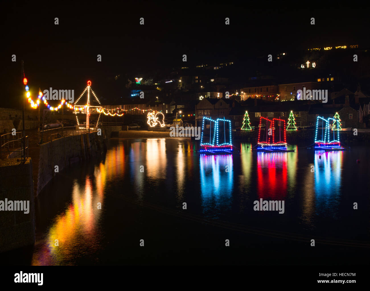 Mousehole, Cornwall, UK. 19th December 2016. The Mousehole harbour lights were turned off for an hour this evening - Stock Image