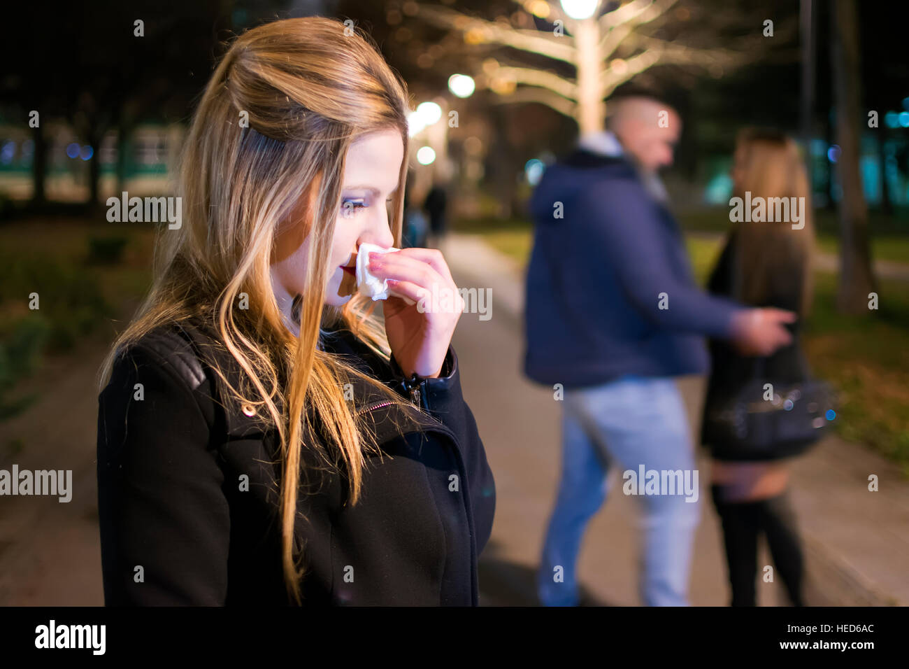 Young Woman Crying in the Night . Betrayal and Infidelity concept. Couple Breaking Up. - Stock Image