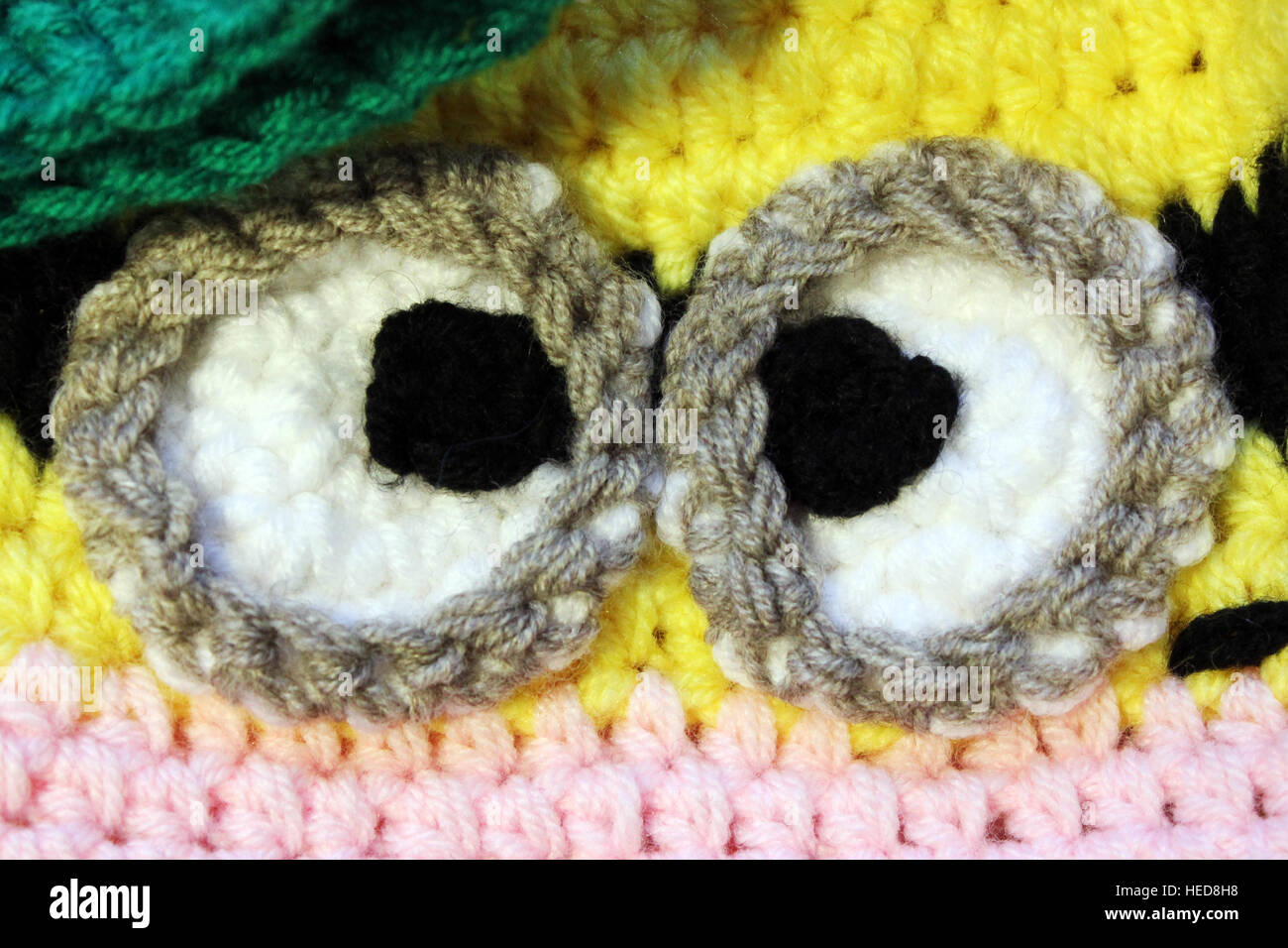 funny eyes associated on a baby hat. - Stock Image