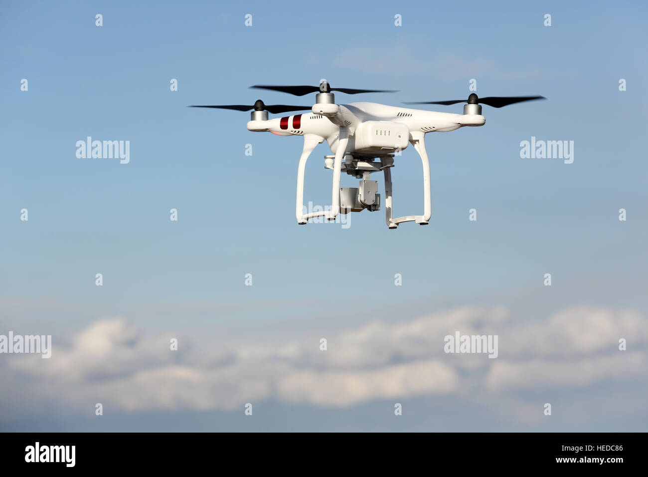 White Remote Controlled Drone Dji Phantom 3 Equipped With High Resolution Video Camera Hovering In Air And Blue Sky