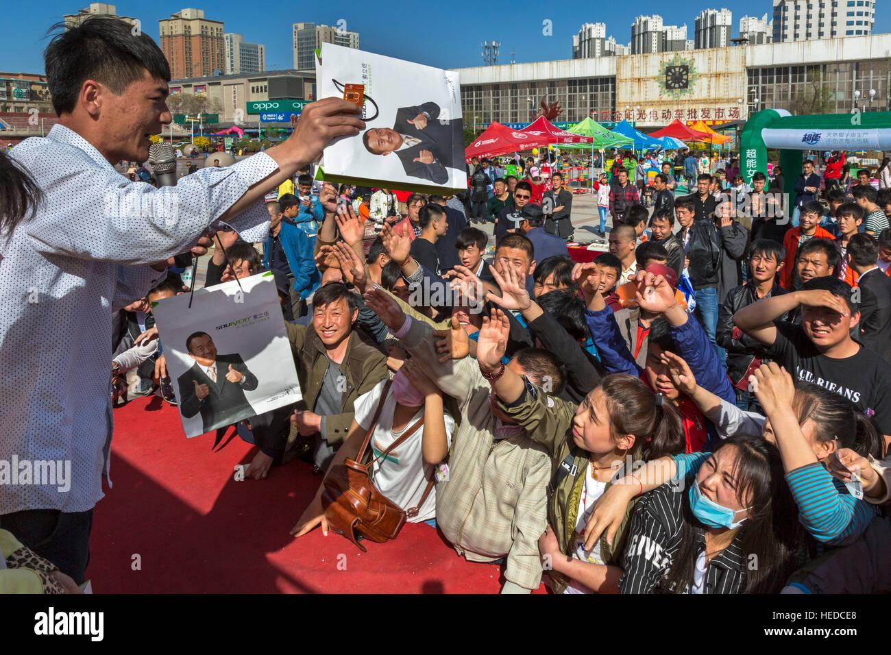 Chinese trader selling at public auction, Nanmen Square, Yinchuan, Ningxia, China - Stock Image