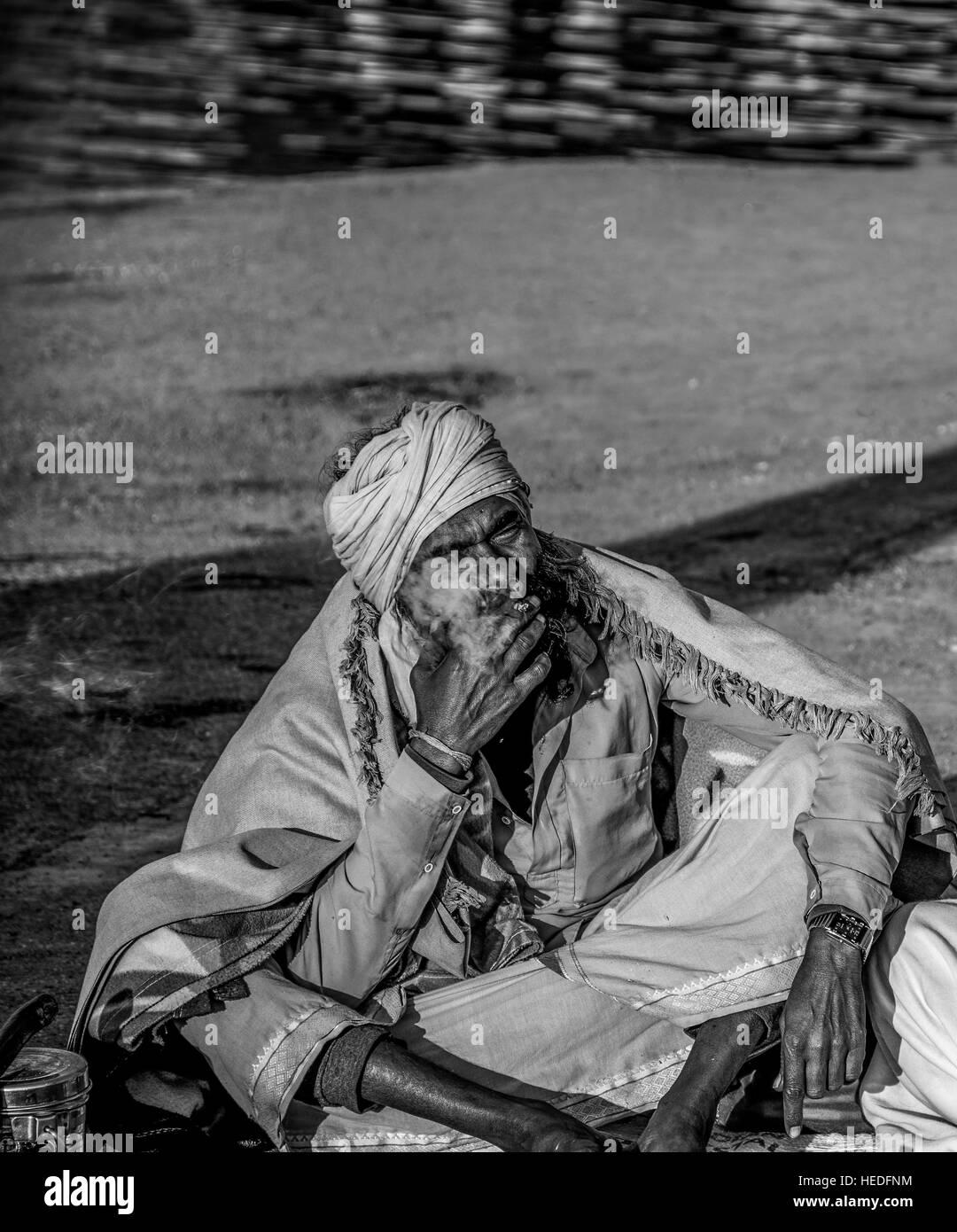 Sadhu enjoying his smoking. - Stock Image