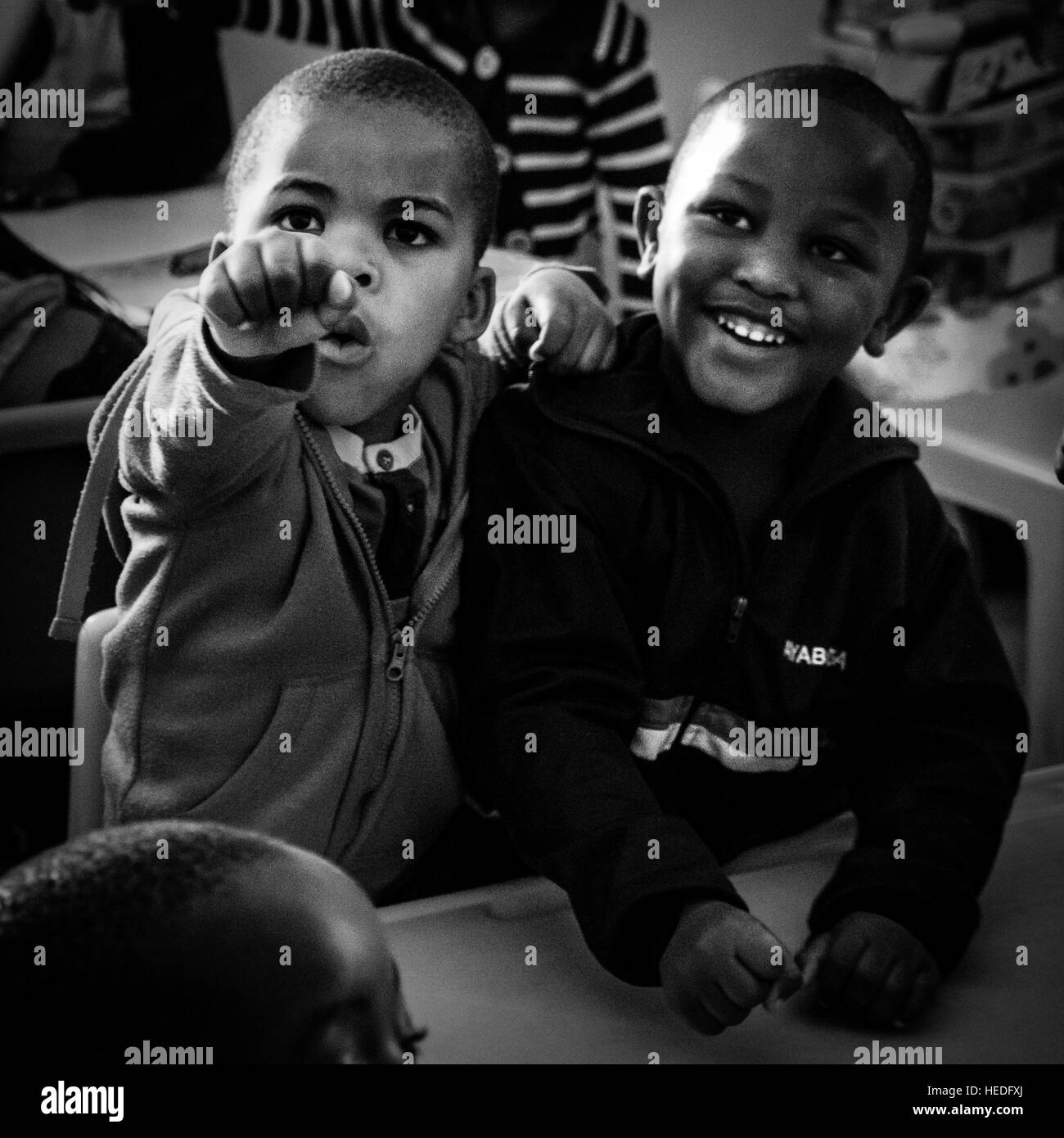 Two children strike a pose in a community supported school in a township in South Africa - Stock Image