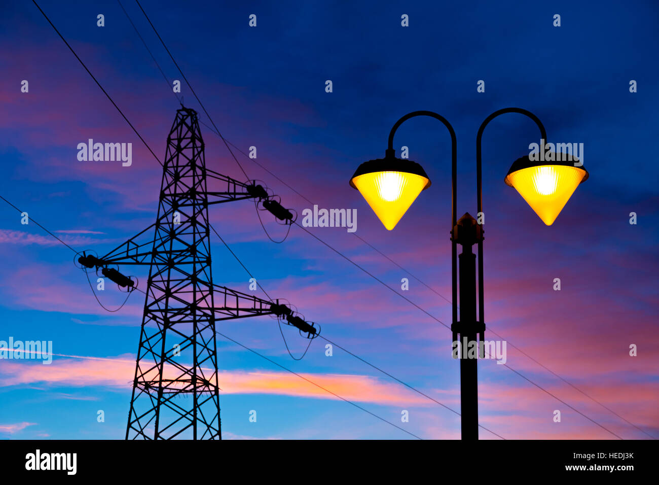 lit on streetlamp at sunset with high-tension line and pylon on the background - Stock Image