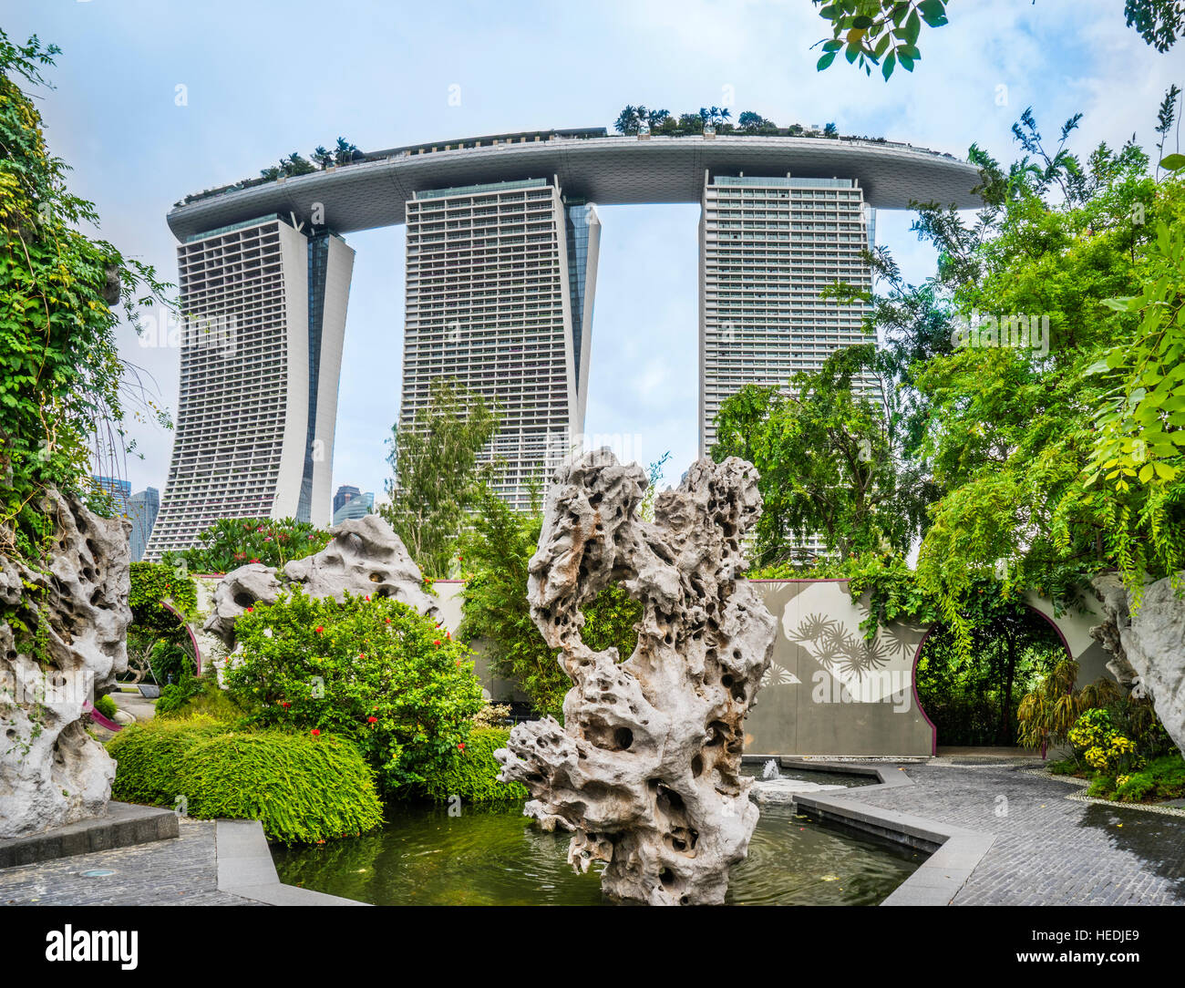 Singapore, sculptured rock at Gardens by the Bay against the backdrop of the Marina Bay Sands resort - Stock Image