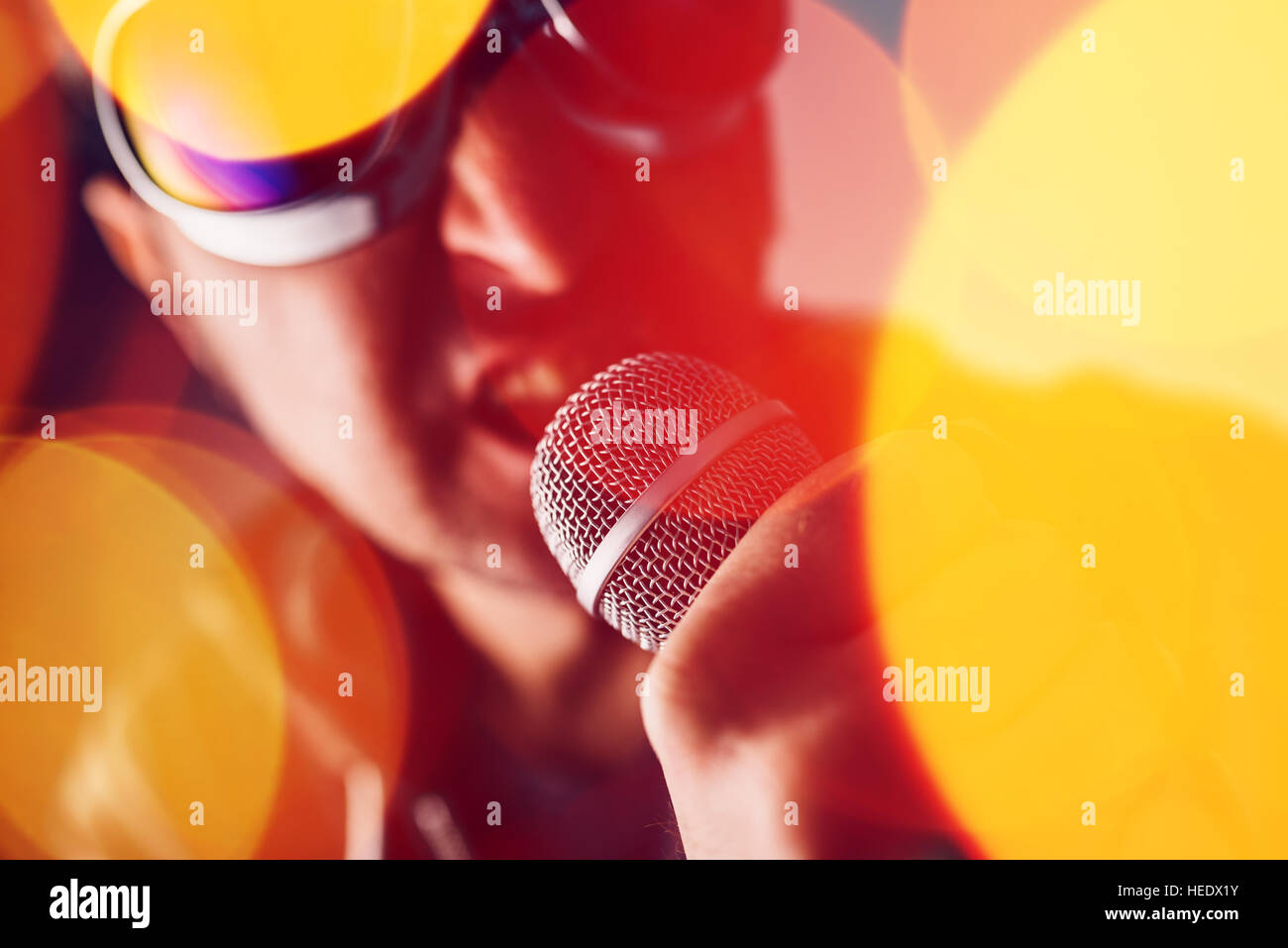Alternative rock music singer singing song into microphone, bokeh light effect and selective focus - Stock Image