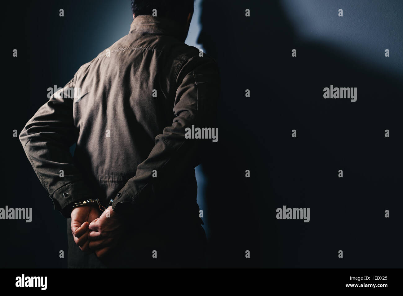 Arrested male criminal with handcuffs facing prison wall as copy space - Stock Image
