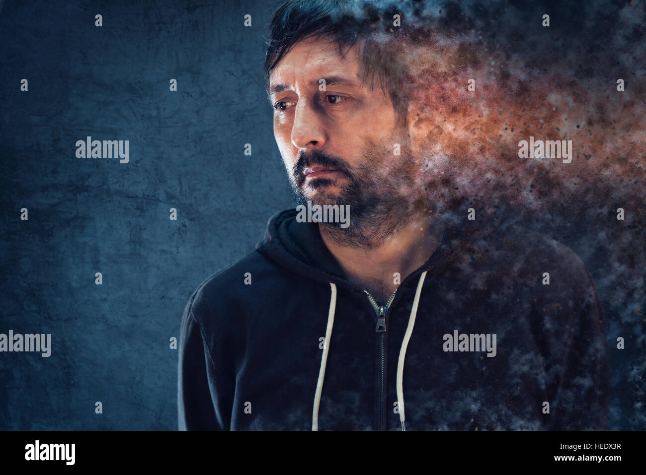 Mental health concept with depressive man dissolving into pieces - Stock Image