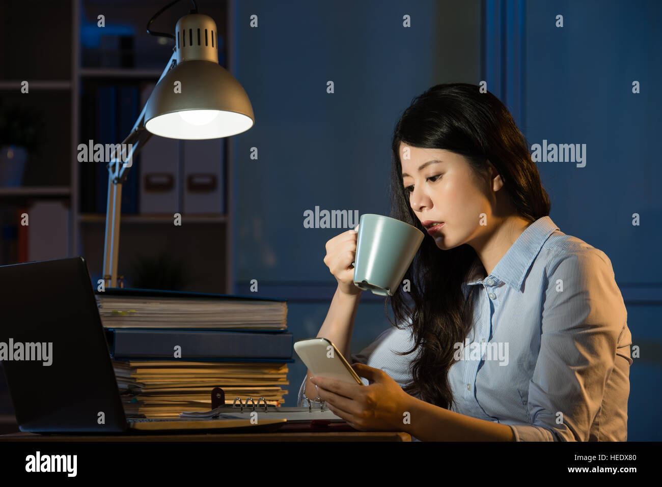 asian business woman talk on smartphone working overtime late night. indoors office background Stock Photo