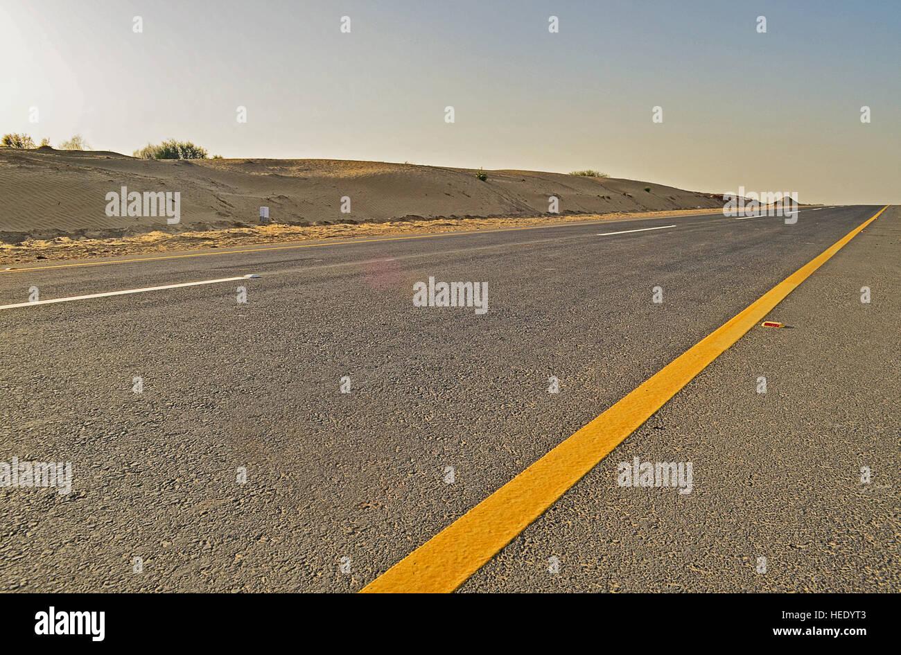 An empty road in a desert terrain - Stock Image