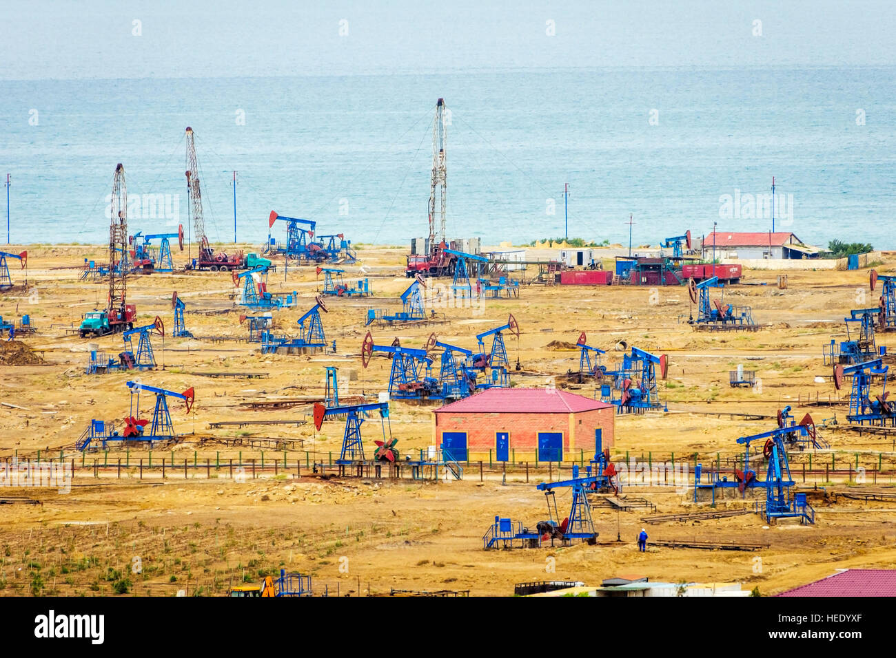 Oil pumps and rigs at the field by Caspian sea near Baku, Azerbaijan - Stock Image