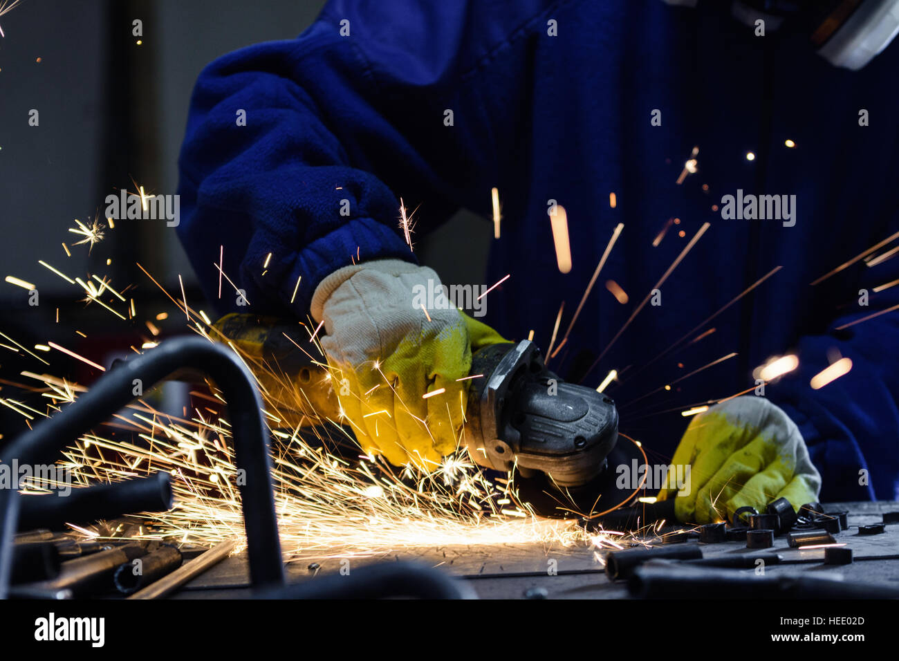 Worker cutting metal on an work table by angle grinder machine tool, generating a flash of hot sparks - Stock Image