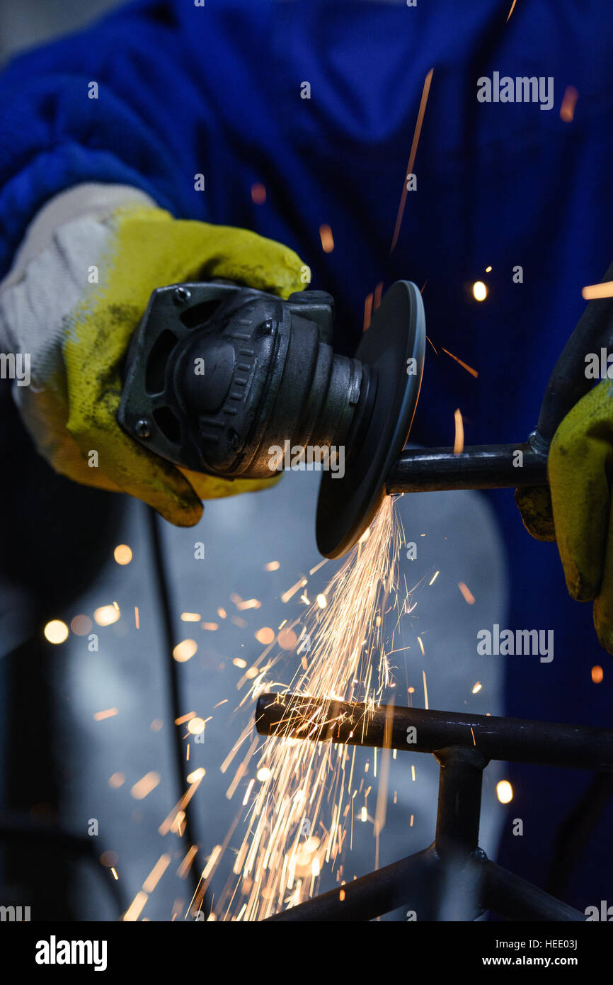 Cutting metal with angle grinder. Sparks flying while grinding pipe - Stock Image