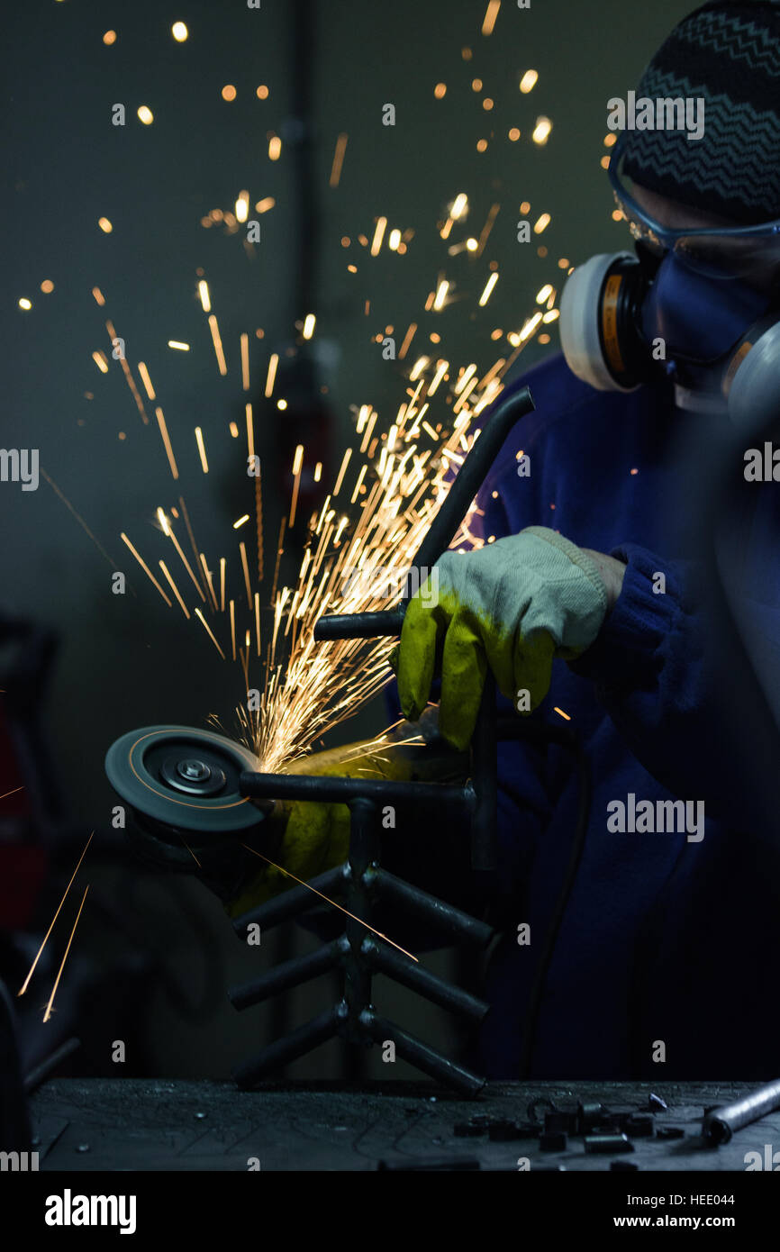 Man cutting steel pipe with an angle grinder producing hot sparks - Stock Image