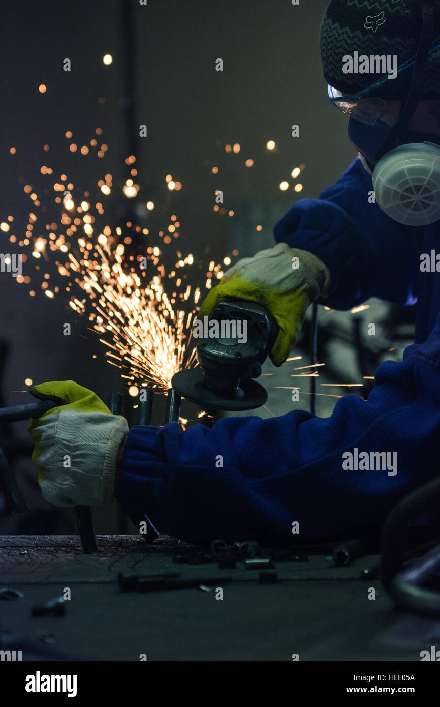 Worker cutting metal and generating sparks by angle grinder machine - Stock Image