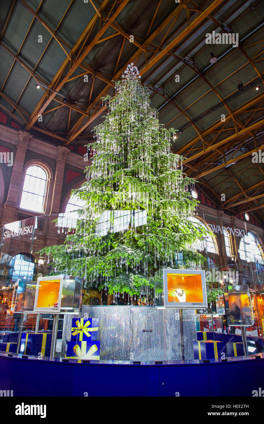 Traditional Christmas market in Zurich railway station with famous Swarovski christmas tree in the background - Stock Image