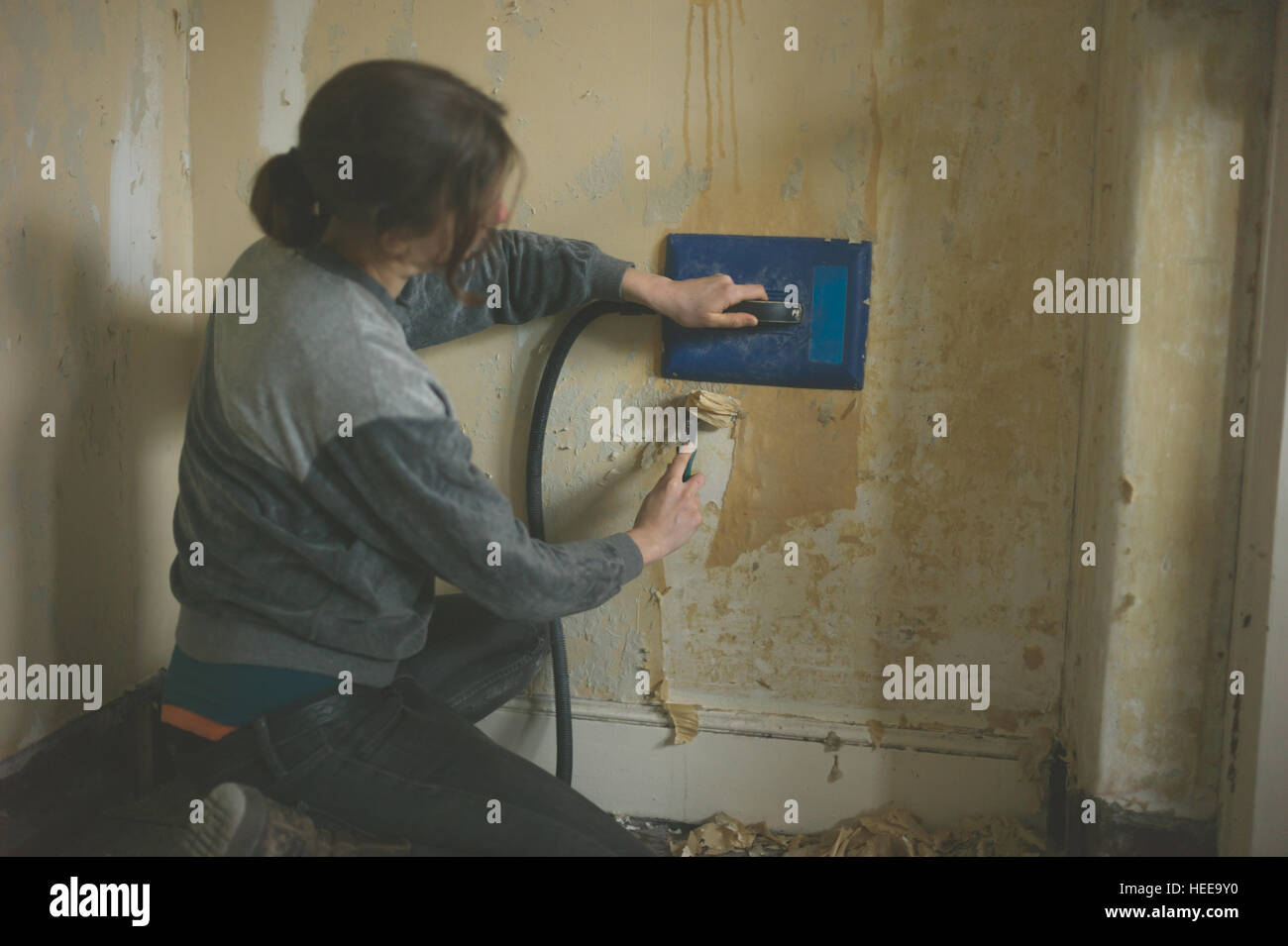 A Young Woman Is Removing Wallpaper With Steamer