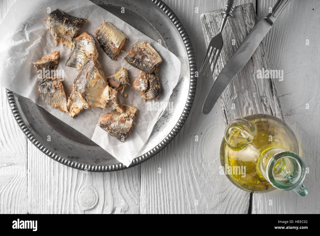 Plate with fish and olive oil on a wooden table horizontal - Stock Image
