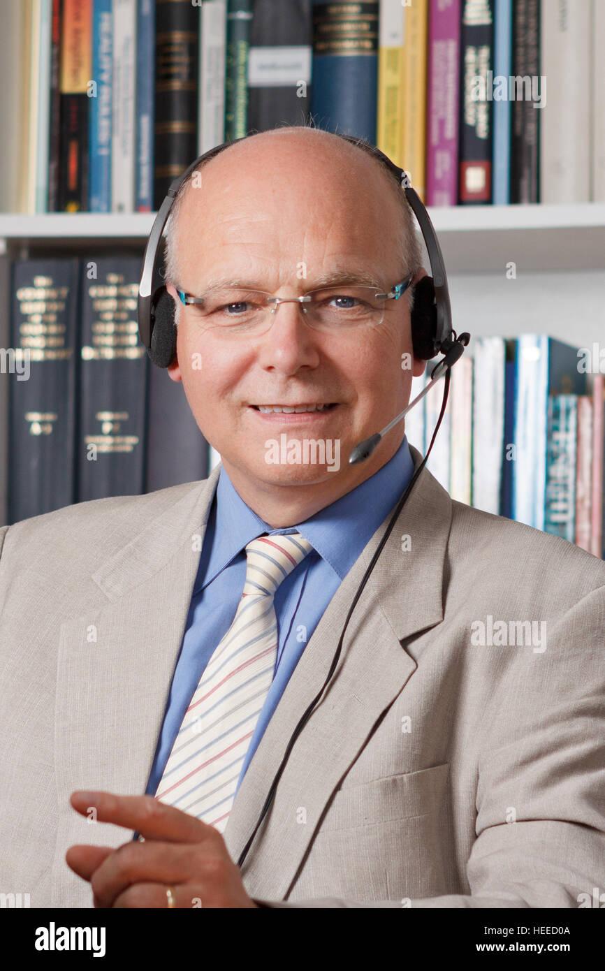 Senior man shirt, jacket, tie and headphones smiling friendly, teacher, tutor, professor, translator, interpreter, - Stock Image