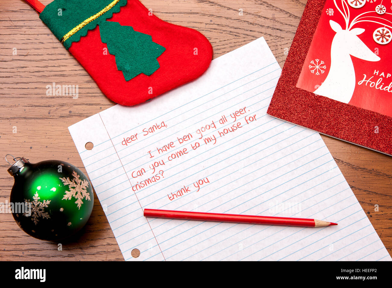 A close up of a letter to Santa and some decorations. - Stock Image