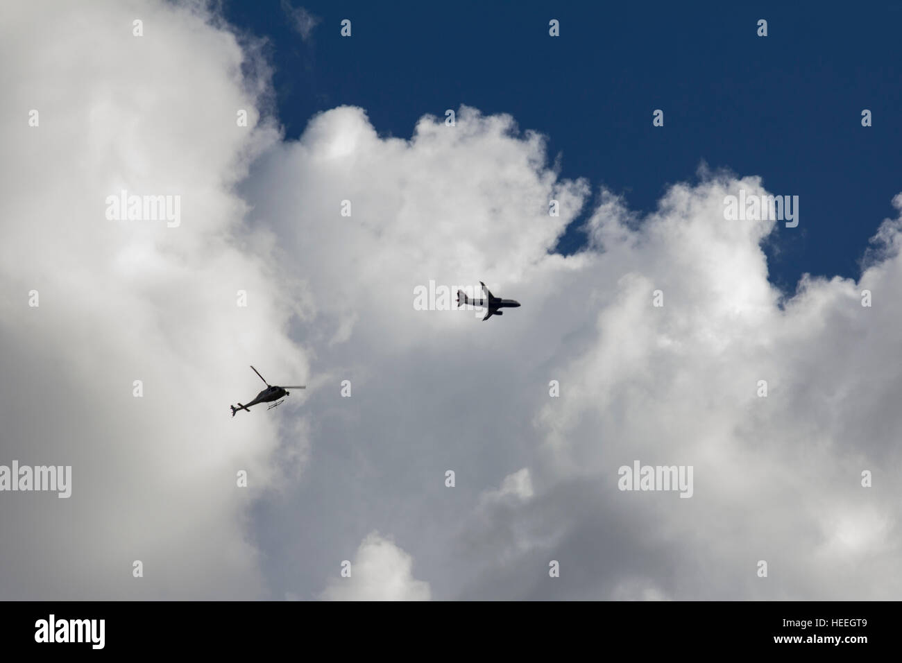 A Helicopter and a plane flying above london - Stock Image