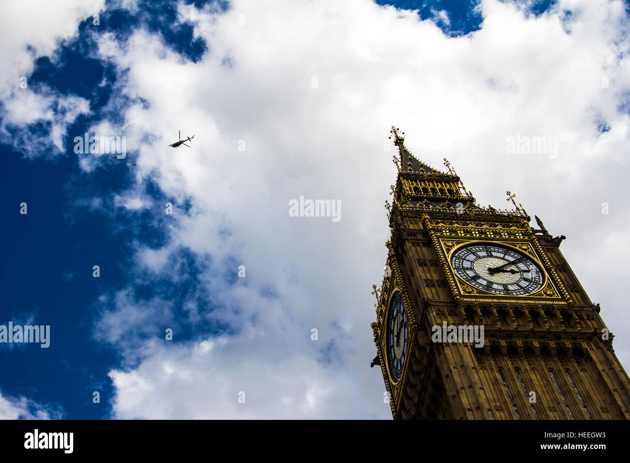 A helicopter flying over the Big Ben in London - Stock Image