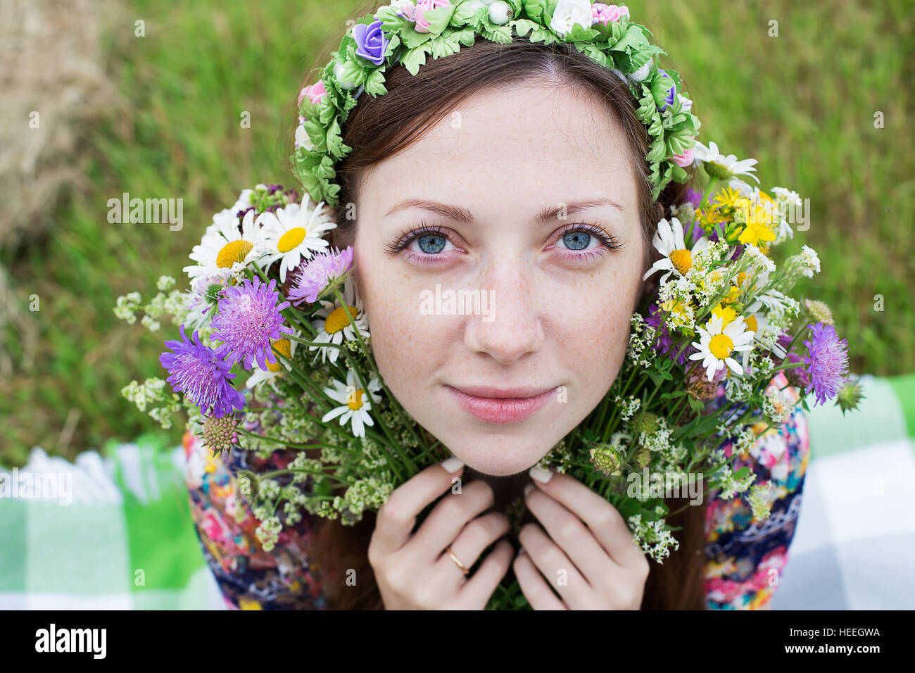Freckled girl sitting with splitting wild flower bouquet - Stock Image