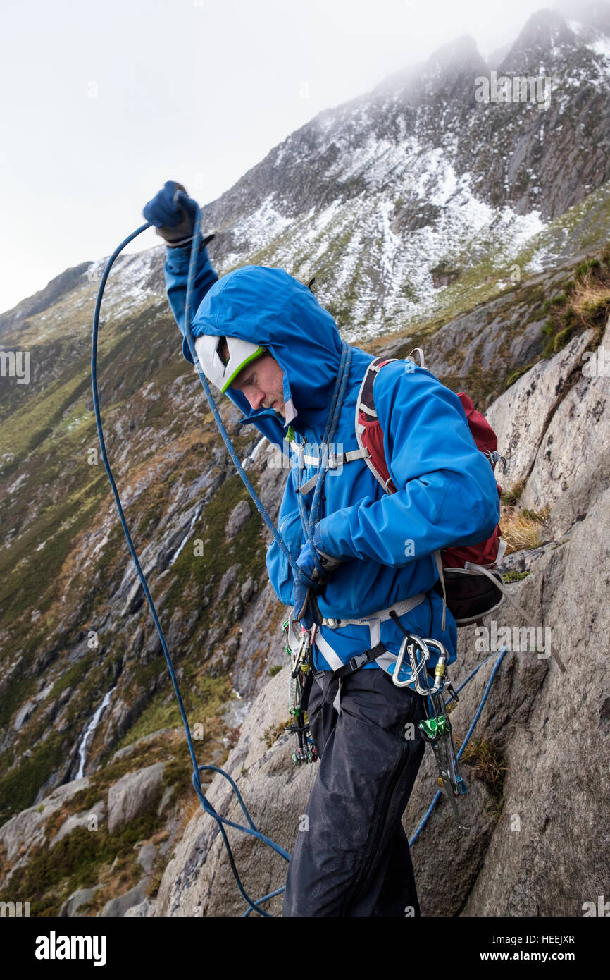 A Mountain Climber Coiling Climbing Rope Around His Body Preparing To Lead Rock Scramble In Cwm Idwal Ogwen Snowdonia North Wales UK Britain