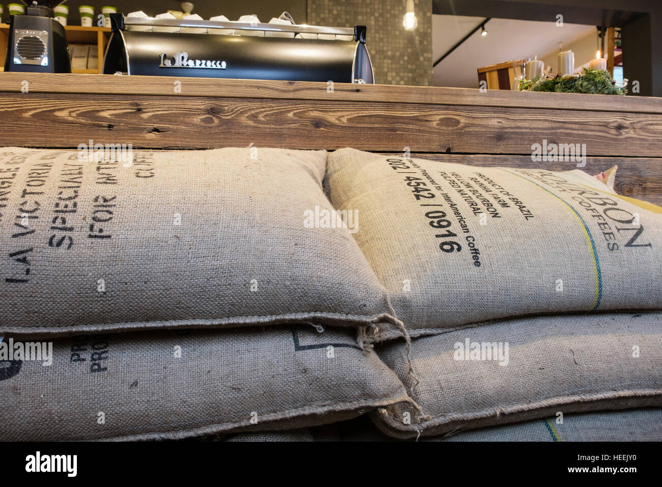 Sacks of fresh Brazilian coffee beans stacked by cafe counter in Bergbrand Rosterei coffee shop. Nuremberg, Bavaria, Stock Photo