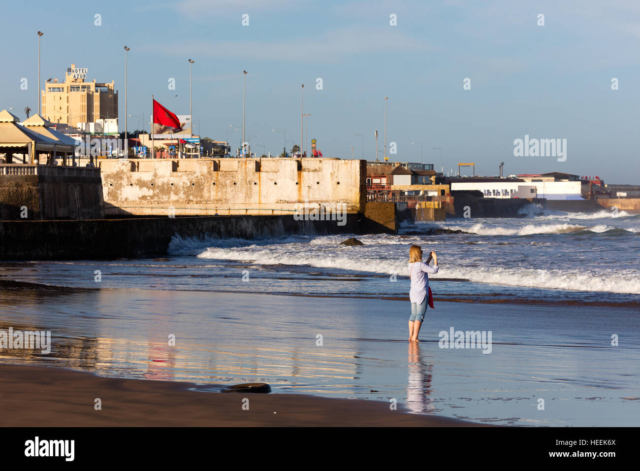 Female tourist shooting selfy, Atlantic ocean beach, Casablanca, Morocco - Stock Image