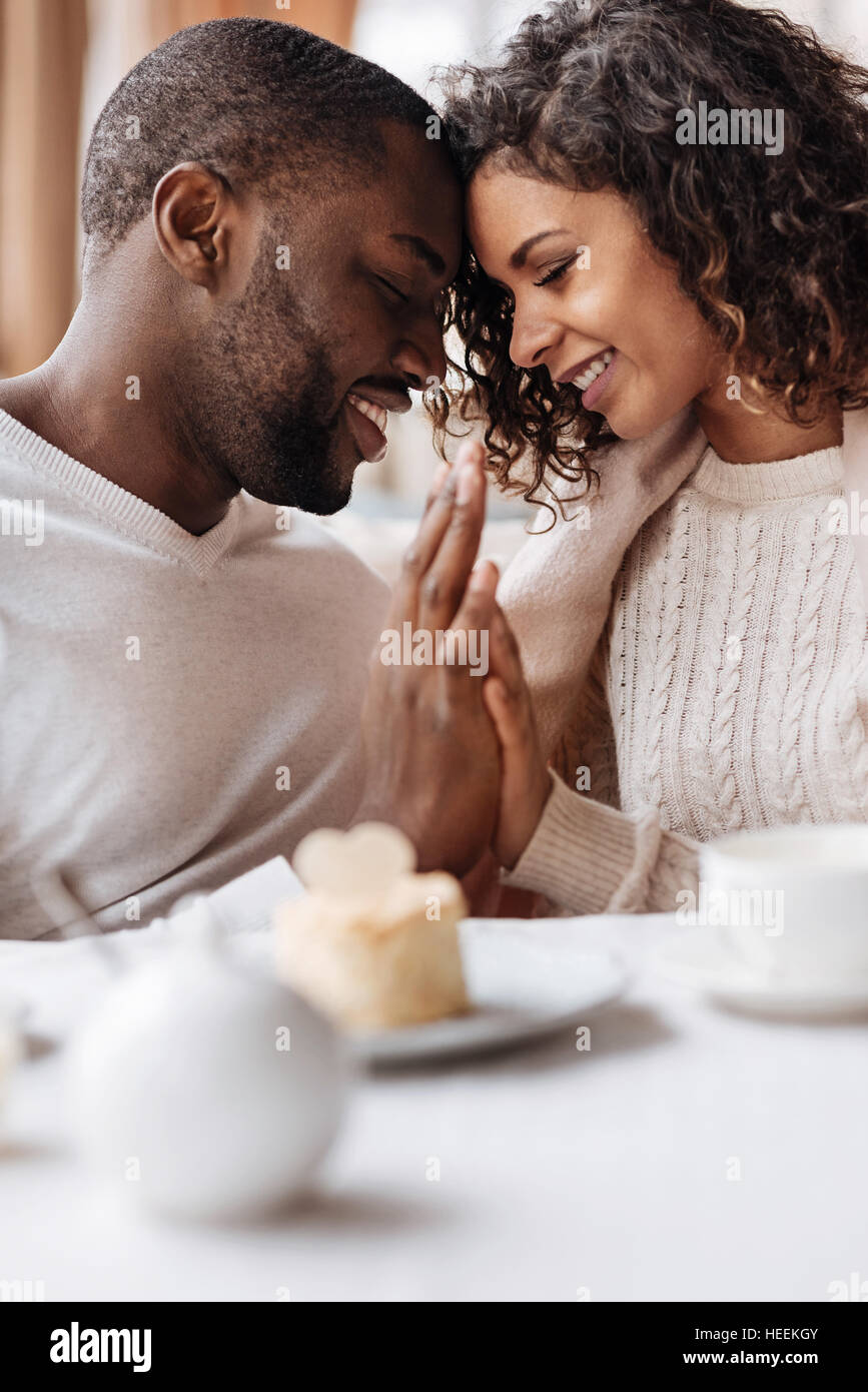 Soulful smiling African American couple touching hands in the cafe - Stock Image