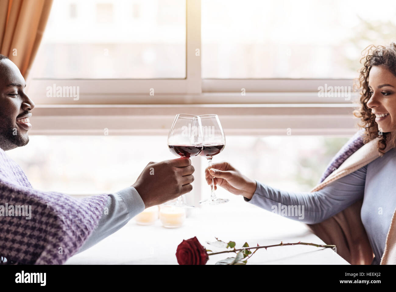 Happy African American couple drinking wine in the restaurant - Stock Image