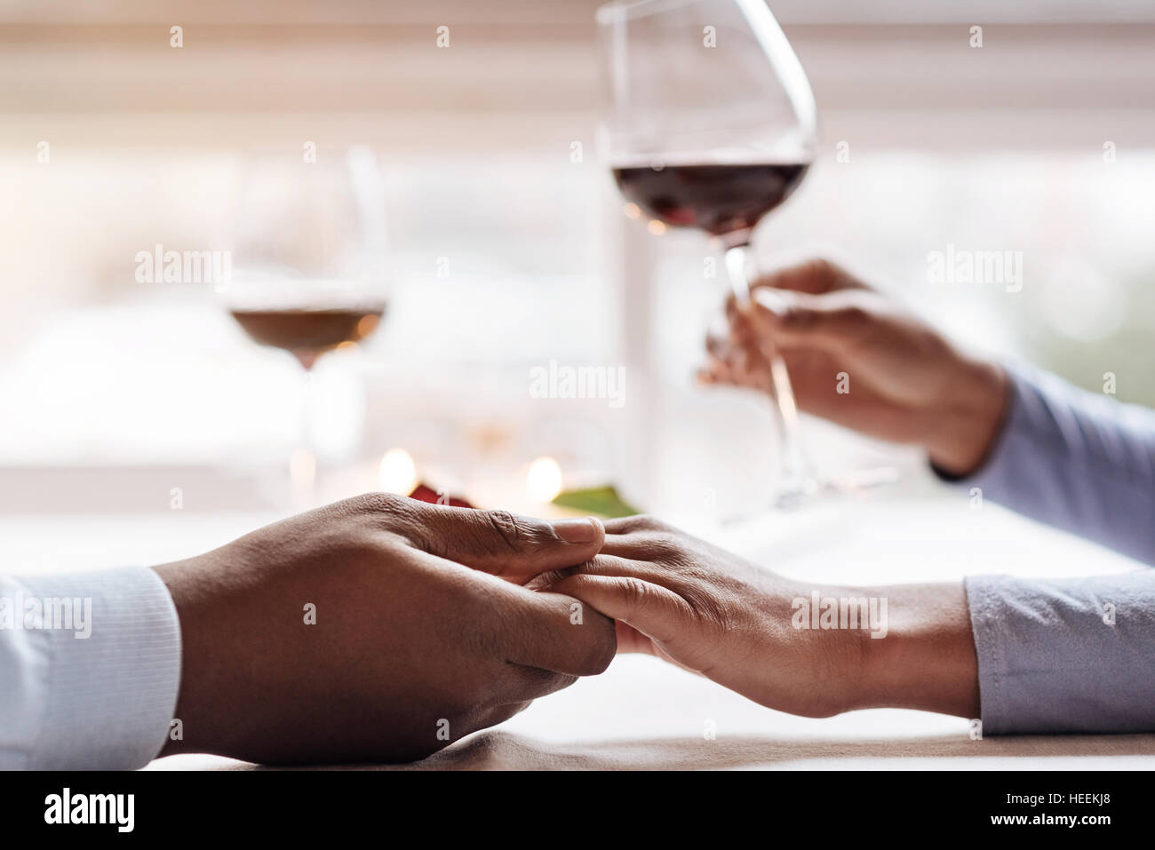 Young African American couple having the date in the restaurant - Stock Image